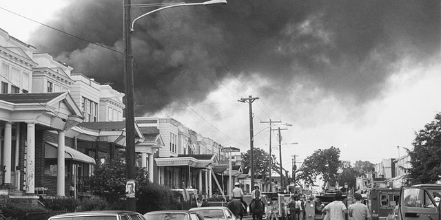 Smoke billows over rowhouses in the West Philadelphia after the police bombed the home of the radical African American organization MOVE during a standoff. Police on horseback and emergency vehicles block off a street as residents walk towards the scene.