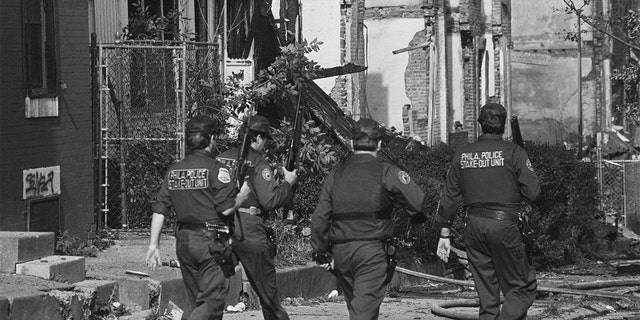 Several Philadelphia police officers patrol the West Philadelphia neighborhood destroyed by the bombing of the MOVE headquarters in 1985.