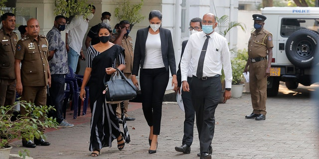 Mrs. World 2019 Caroline Jurie, center, leaves a police station after obtaining bail in Colombo, Sri Lanka, Thursday, April 8, 2021. Jurie's decision to remove the crown from the the winning Mrs. Sri Lanka contestant on stage moments after the winner was announced, because of claims she was a divorcee, drew widespread social media condemnation. The winner Pushpika de Silva who was crowned again later had complained to police that her head was wounded when the clips of her crown were removed by Jurie.
