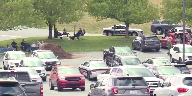 Police set up a staging area at the Mount Vernon Baptist Church, which is also the site of a school that was placed on lockdown amid an ongoing standoff at a nearby home.