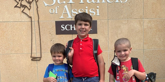 Nathan Herber, his twin bother Justin, and older brother Grant at St. Francis of Assisi in Rochester, Minnesota.