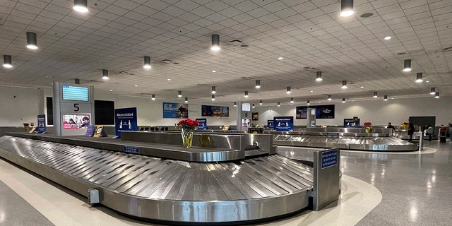 Empty baggage carousels in Terminal 2 of the Oakland International Airport, Friday Dec. 25, 2020, in Oakland, California.