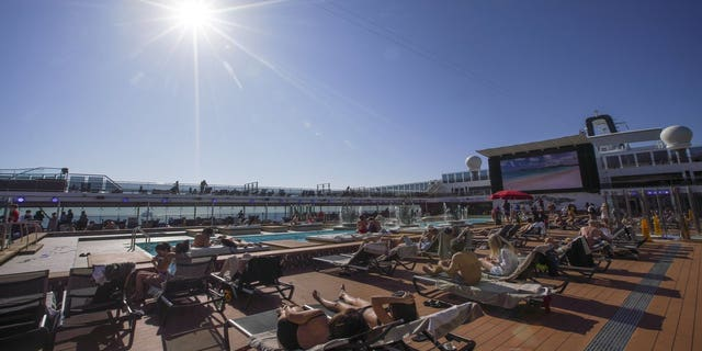 Guests lounge near a pool on the MSC Grandiosa as the rest of Italy is heading back into full lockdown over the Easter weekend, with shops closed and restaurants and bars open for takeout only to try to minimize holiday outbreaks. (AP Photo/Andrew Medichini)