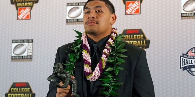 FILE - In this Dec. 12, 2019, file photo, Oregon's Penei Sewell poses with Outland Trophy for being the nation's best interior lineman, in Atlanta. Sewell is a likely first-round pick in the NFL Draft, April 29-May 1, 2021, in Cleveland.(AP Photo/John Bazemore, File)
