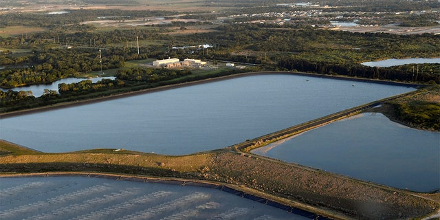 This photo shows the reservoir near the old Piney Point Phosphate Mine in Bradenton, Florida on Saturday, April 3, 2021. Florida Governor Ron DeSantis declared a state of emergency on Saturday. Blasted a system storing contaminated water. The pond where the leak was found is located in the ancient Piney Point phosphate mine, in a pile of phosphogypsum, a waste product from the production of radioactive fertilizers.  (Tiffany Tompkins/Bradenton Herald via AP)