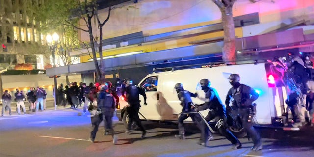 Riot police run towards protesters in Portland, Oregon, U.S. April 16, 2021, in this still image taken from a video. Grace Morgan via REUTERS THIS IMAGE HAS BEEN SUPPLIED BY A THIRD PARTY. MANDATORY CREDIT. NO RESALES. NO ARCHIVES.