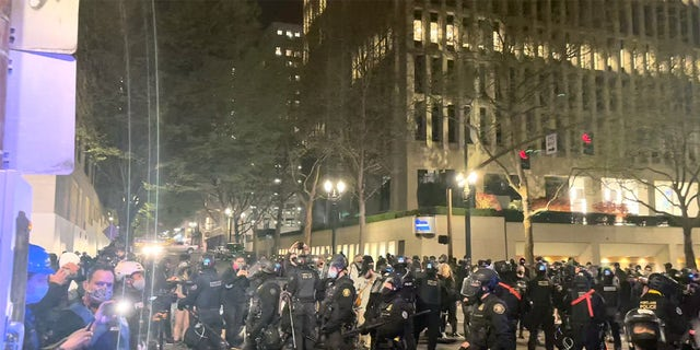 Riot police members stand guard during protests in Portland, Oregon, U.S. April 16, 2021, in this still image taken from a video. Grace Morgan via REUTERS THIS IMAGE HAS BEEN SUPPLIED BY A THIRD PARTY. MANDATORY CREDIT. NO RESALES. NO ARCHIVES.