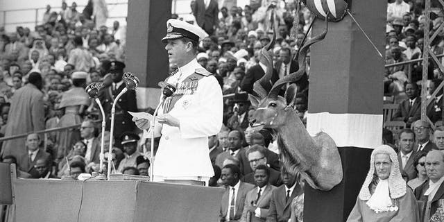 In this Dec. 12, 1963, file photo, Britain's Prince Philip delivers an address before handing over to Jomo Kenyatta, prime minister of Kenya, during the ceremony of Independence at Uhuru Stadium in Nairobi. (AP Photo/Dennis Royle, File)