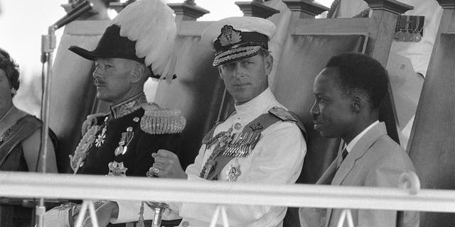 In this Dec. 9, 1961, file photo, Britain's Prince Philip, center, looks at Tanganyika Prime Minister Julius Nyerere, right, during the ceremony to swear in the new governor-general at the Independence celebrations in Dar-Es-Salaam, Tanganyika. (AP Photo/File)