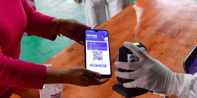medical worker scans QR code on the mobile phone screen for registration before a resident receives nucleic acid testing for COVID-19 at Munao community, Ruili City, southwest China's Yunnan Province, April 6, 2021. (Xinhua/Chen Xinbo via Getty Images)