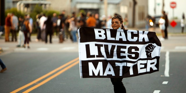 A protester carries a Black Lives Matter flag shortly before the start of a dawn to dusk curfew following the killing of Andrew Brown Jr. by sheriffs last week, in Elizabeth City, North Carolina, U.S. April 27, 2021. REUTERS/Jonathan Drake