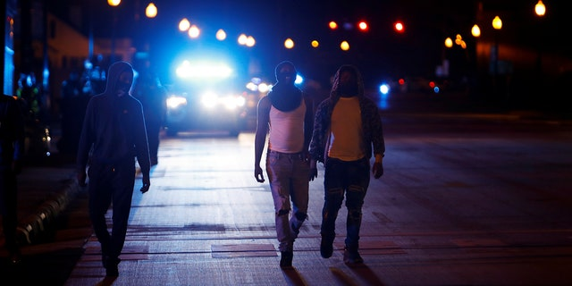 Protesters walk away from police vehicles as a few demonstrators ignore the dawn to dusk curfew following the killing of Andrew Brown Jr. by sheriffs last week, in Elizabeth City, North Carolina, U.S. April 27, 2021. REUTERS/Jonathan Drake