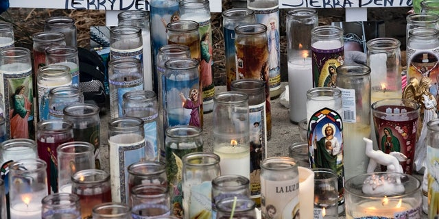 Candles and crosses are placed as a memorial for three children who were killed at the Royal Villa apartments complex in the Reseda section of Los Angeles.