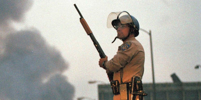 A California Highway Patrol officer stands guard at Ninth Street and Vermont Avenue in Los Angeles as smoke rises from a fire further down the street, April 30, 1992. It was the second day of unrest in Los Angeles following the acquittal of four Los Angeles police officers in the Rodney King beating case. (AP Photo/David Longstreath)