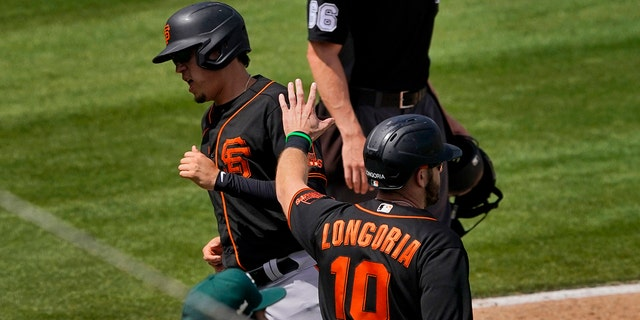 San Francisco Giants' Wilmer Flores and Evan Longoria (10) score on a double hit by Curt Casali during the third inning of a spring training baseball game against the Oakland Athletics, Monday, March 29, 2021, in Mesa, Ariz. (AP Photo/Matt York)