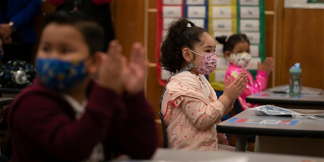 First graders applaud while listening to their teach in a classroom on the first day of in-person learning at Heliotrope Avenue Elementary School in Maywood, California, Tuesday, April 13, 2021. (AP Photo/Jae C. Hong)