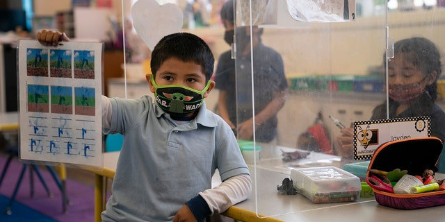 FILE - In this March 18, 2021, file photo, Cesar Verdugo, 5, shows his work to his teacher in a pre-kindergarten class at West Orange Elementary School in Orange, Calif. (AP Photo/Jae C. Hong, File)
