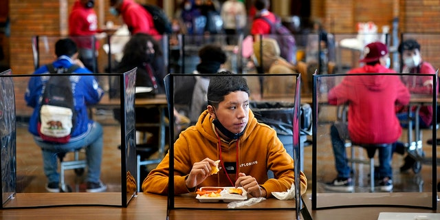 Freshman Hugo Bautista eats lunch separated from classmates by plastic dividers at Wyandotte County High School in Kansas City, Kan., on the first day of in-person learning. (AP Photo/Charlie Riedel, File)