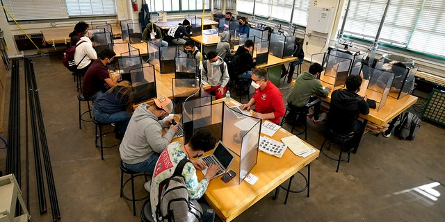 Wyandotte County High School are separated by plastic dividers on the first day of in-person learning at the school in Kansas City, Kan. (AP Photo/Charlie Riedel, File)