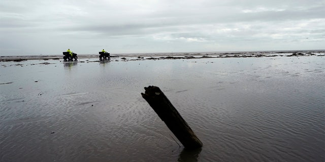 Lafourche Parish deputies patrol along the shoreline of the Gulf of Mexico, not far from where a lift boat capsized during a storm on Tuesday, killing one with 12 others still missing, on Elmer's Island, La., Thursday, April 15, 2021. (AP Photo/Gerald Herbert)