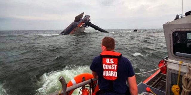 In this photo provided by the U.S. Coast Guard, A Coast Guard Station Grand Isle 45-foot Response Boat-medium boat crew member searches for survivors near the capsized SeaCor Power. (U.S. Coast Guard via AP)