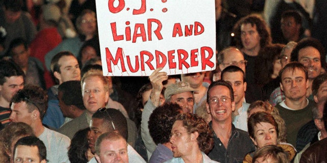 SANTA MONICA, UNITED STATES: Spectators outside the Santa Monica, California, courthouse, hold an-anti O.J Simpson placard as they react to the guilty verdicts in the Simpson wrongful death civil trial 04 February. Simpson was found liable for the deaths of his ex-wife Nicole Brown Simpson and her friend Ron Goldman. (Photo credit should read HECTOR MATA/AFP via Getty Images)