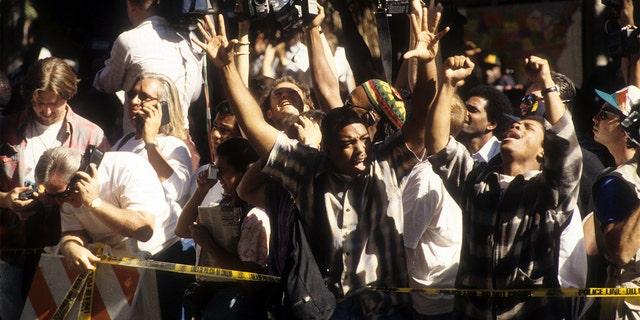 The crowd cheers after hearing the decision of the O.J. Simpson verdict at the Los Angeles Courthouse on October 3, 1995. (Photo by Michael Montfort/Michael Ochs Archives/Getty Images)