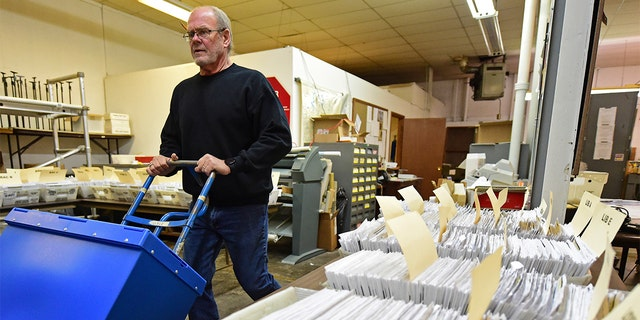 This Tuesday, Nov. 3, 2020 file photo shows Board of Elections worker Bob Moody moving boxes of ballots at the Trumbull County Board of Elections in Warren, Ohio.