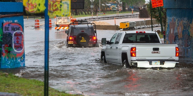 Trucks make their way through high water Saturday, April 10, 2021, at the Graffiti Bridge in Pensacola after a powerful storm swept through the area.Saturday Storm 1
