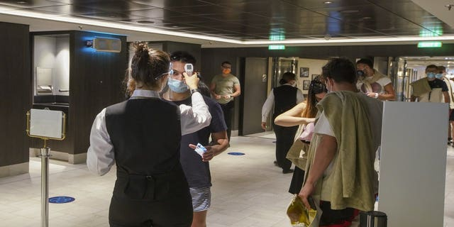 Passengers have their body temperature measured as they enter a restaurant of the MSC Grandiosa cruise ship in Civitavecchia, near Rome, Wednesday, March 31, 2021.(AP Photo/Andrew Medichini)