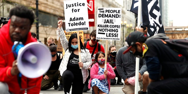 Abigail Garcia, 7, right, takes a knee with her mother Judith Garcia and other protestors during a peaceful protest on Tuesday, April 13, 2021, in downtown Chicago, demanding justice for Daunte Wright and Adam Toledo, who were shot dead by police. (AP Photo/Shafkat Anowar)