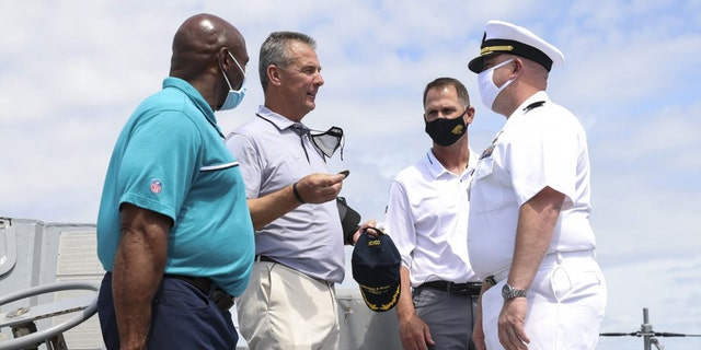 Urban Meyer hands a ceremonial coin to Cmdr. Matthew McKenna.