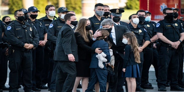 Family members hug after the casket of Evans was carried from the Capitol on Tuesday. (AP/The Washington Post)