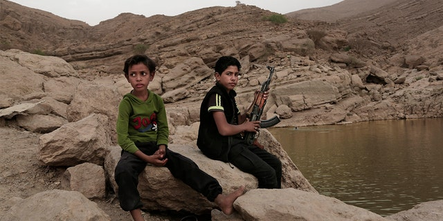 In this July 30, 2018 photo, a 17-year-old boy holds his weapon at the dam in Marib, Yemen.