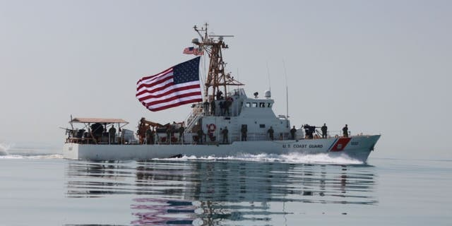 Coast Guardsmen aboard the U.S. Coast Guard cutter USCGC Adak raise the American flag. (U.S. Coast Guard photo by Seaman Frank Iannazzo-Simmons/Released)