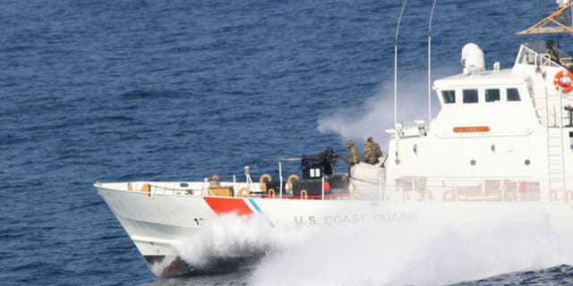 U.S. Coast Guardsmen aboard the Coast Guard patrol boat USCGC Adak stand security watch during a Strait of Hormuz transit, Dec. 8, 2020. (U.S. Navy photo by Mass Communication Specialist 2nd Class Indra Beaufort)