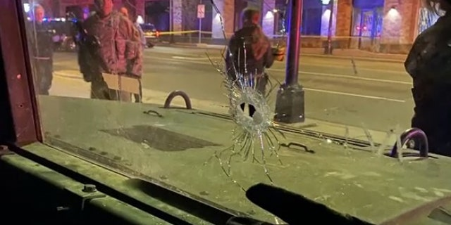 Minnesota National Guard stands near bullet hole in window.