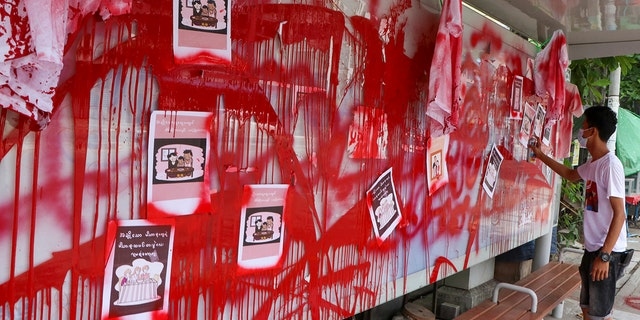 """An anti-coup protester uses red paint as he writes slogans at a bus stop on Wednesday April 14, 2021 in Yangon, Burma. Anti-coup protesters kept public demonstrations going despite the threat of lethal violence from security forces. The words reads """"We do not accept military coup"""". (AP Photo)"""