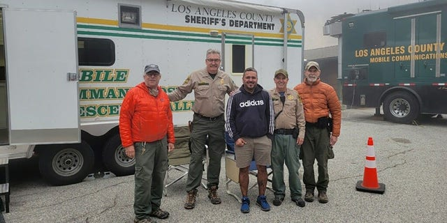 Compean, center, posed for a photo with his rescuers after he was found safe and airlifted off the mountain.