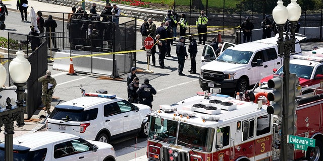 Police and fire officials stand near a car that crashed into a barrier on Capitol Hill in Washington, Friday, April 2, 2021. (AP Photo/J. Scott Applewhite)