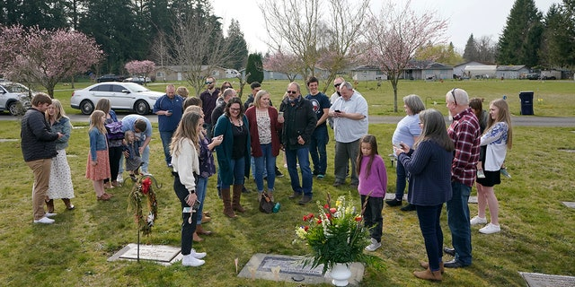 March 27, 2021: Family members and friends sing as they gather around the headstone Carole Rae Woodmansee shares with her husband Jim (who died in 2003) at Union Cemetery in Sedro-Woolley, Wash., north of Seattle, following a memorial service.
