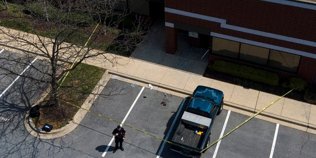 An official stands near a taped-off area near the scene of a shooting at a business park in Frederick, Md. (AP Photo/Julio Cortez)