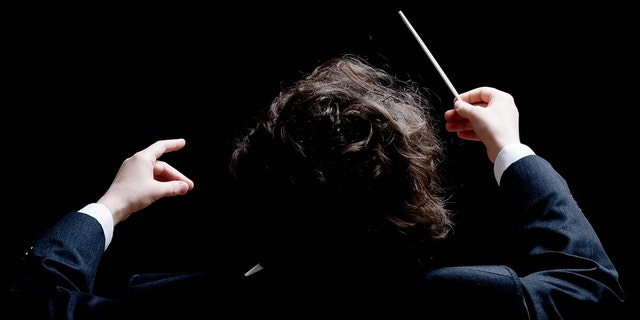 A conductor's hands with a baton.