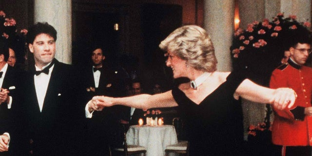 Diana, Princess Of Wales, wearing a midnight blue velvet, off the shoulder evening gown designed by Victor Edelstein, is watched by US President Ronald Reagan and First Lady Nancy Reagan, as she dances with John Travolta at the White House on November 9, 1985 in Washington, DC.