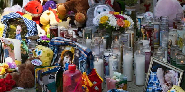 Photos, candles, flowers and balloons are placed as a memorial for three children who were killed at the Royal Villa apartments complex in the Reseda section of Los Angeles, on Monday, April 12, 2021. (AP Photo/Richard Vogel)