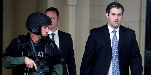 FILE- In this Dec. 5, 2016 file photo, Michael Slager, at right, walks from the Charleston County Courthouse under the protection from the Charleston County Sheriff's Department after a mistrial was declared for his trial in Charleston, S.C. (AP Photo/Mic Smith, File)