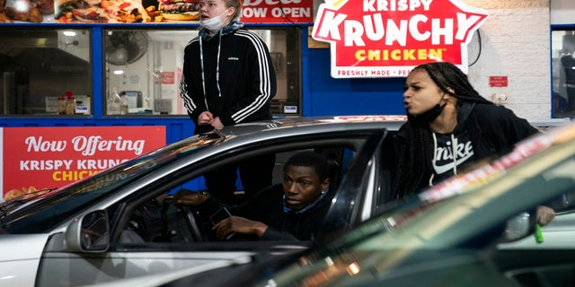 Drivers react as a line of police advances into a gas station in an effort to push back demonstrators gathered for a protest against the police shooting of Daunte Wright, late Monday, in Brooklyn Center, Minn. (AP)