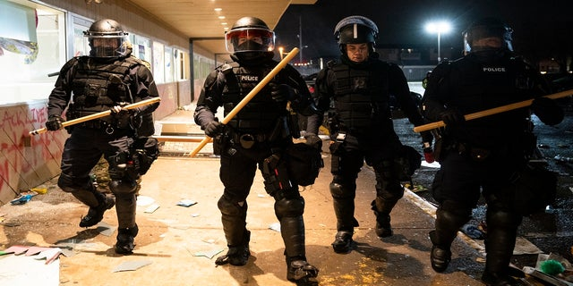 Police clear a strip mall of demonstrators after issuing orders to disperse late Monday in Brooklyn Center, Minn. (AP)