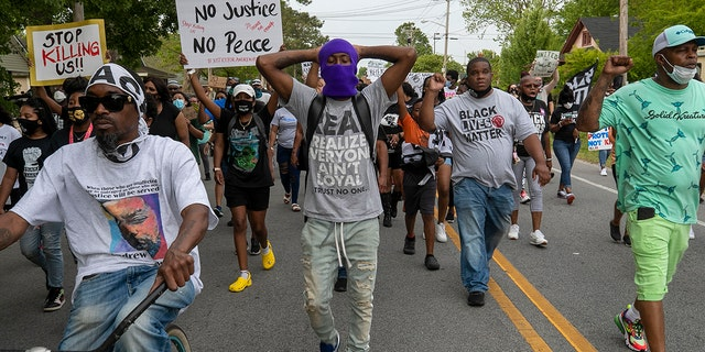 Elizabeth City Councilman Gabriel Adkins, second from right wearing a Black Lives Matter shirt, helps lead demonstrators on a march through Andrew Brown Jr.'s neighborhood, Thursday, April 29, 2021, in Elizabeth City, N.C. (Robert Willett/The News & Observer via AP)