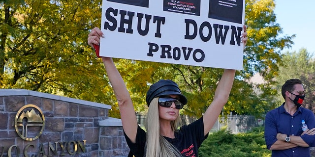 Paris Hilton poses for a photo in front of the Provo Canyon School during a protest Friday, Oct. 9, 2020, in Provo, Utah. Hilton was in Utah Friday to lead a protest outside a boarding school where she alleges she was abused physically and mentally by staff when she was a teenager. Hilton, now 39, went public with the allegations in a new documentary and wants a school that she says left her with nightmares and insomnia for years to be shut down.